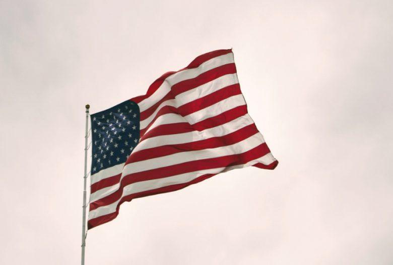 US flag grey skies behind