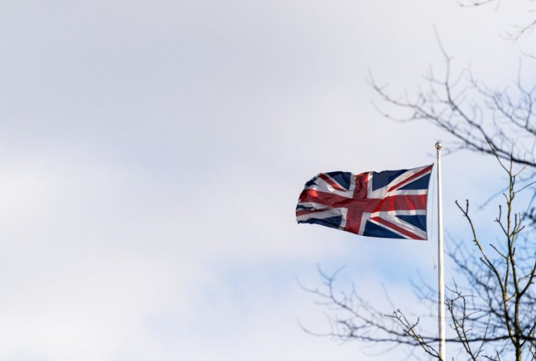 British flag pole with tree behind